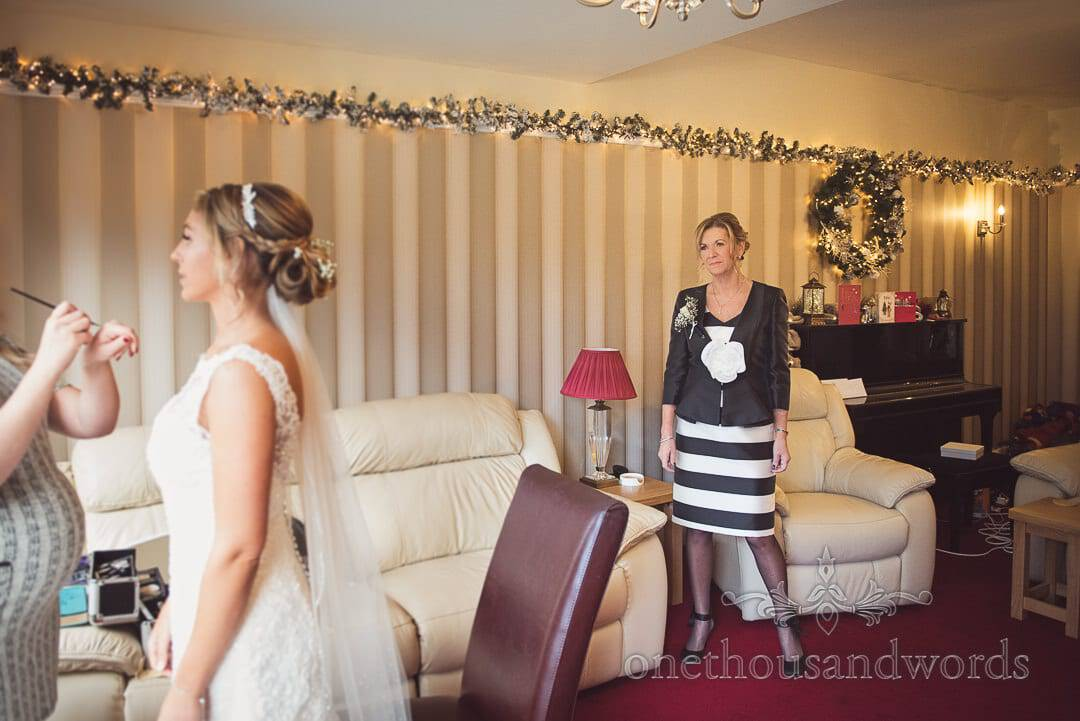 Mother of bride in Black and white wedding outfit watches bride's final wakeup adjustments