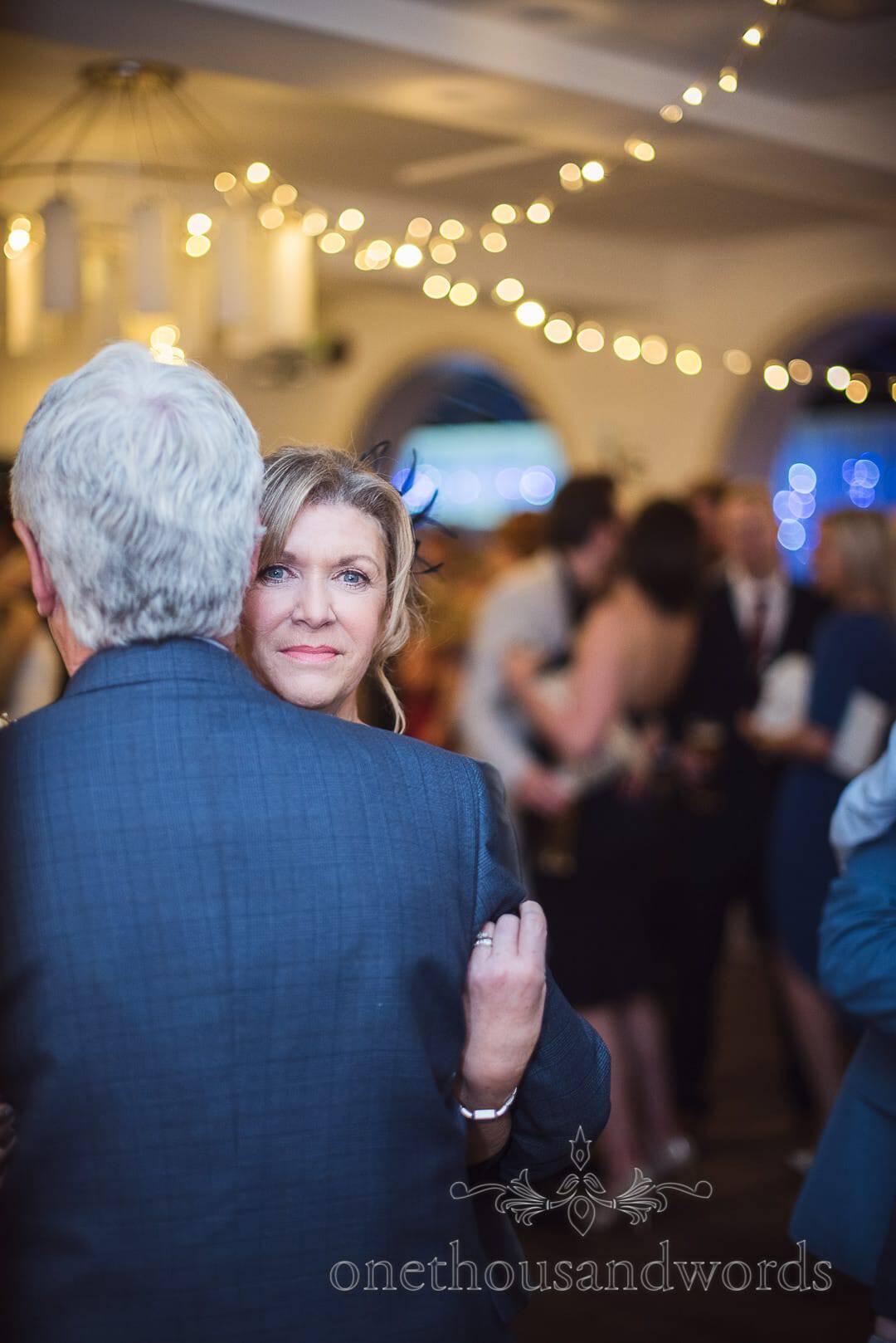 Mother of the bride dances under fairy lights at The Italian Villa Wedding Venue