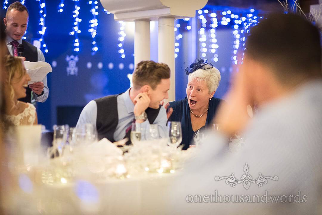 Mother of the Groom is shocked by best man's speech in front of blue Christmas lights