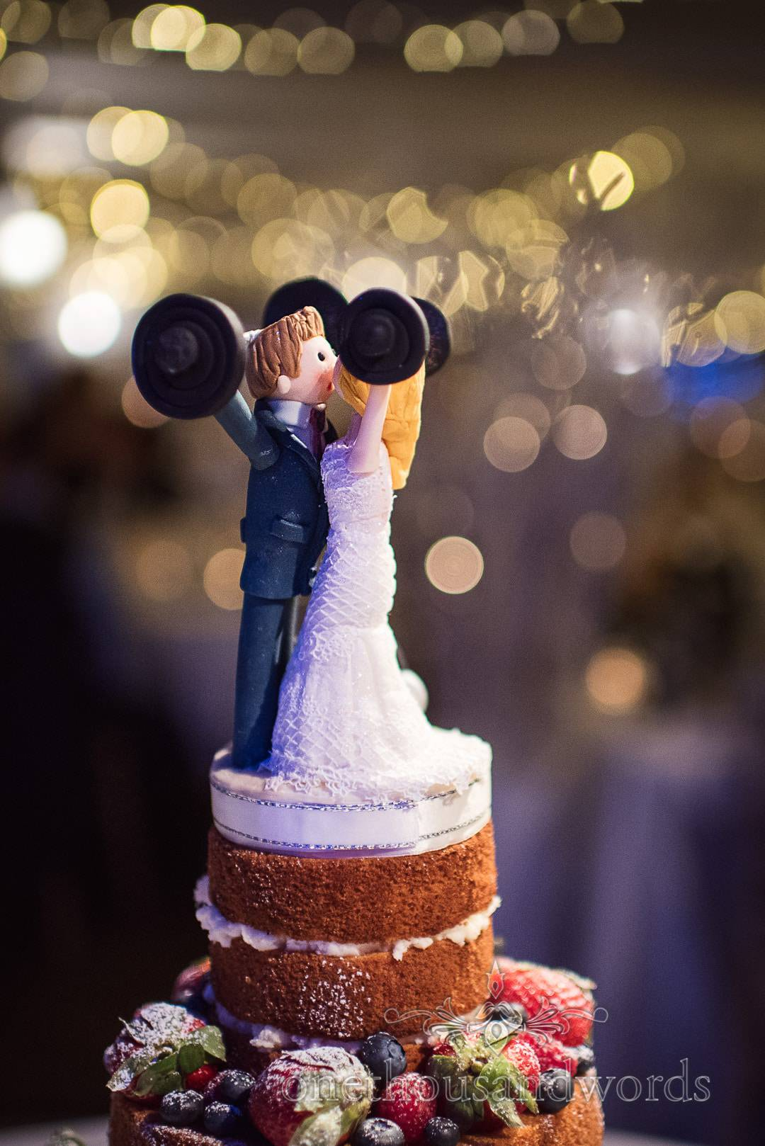 Naked wedding cake topper of bride and groom kissing whilst lifting weights
