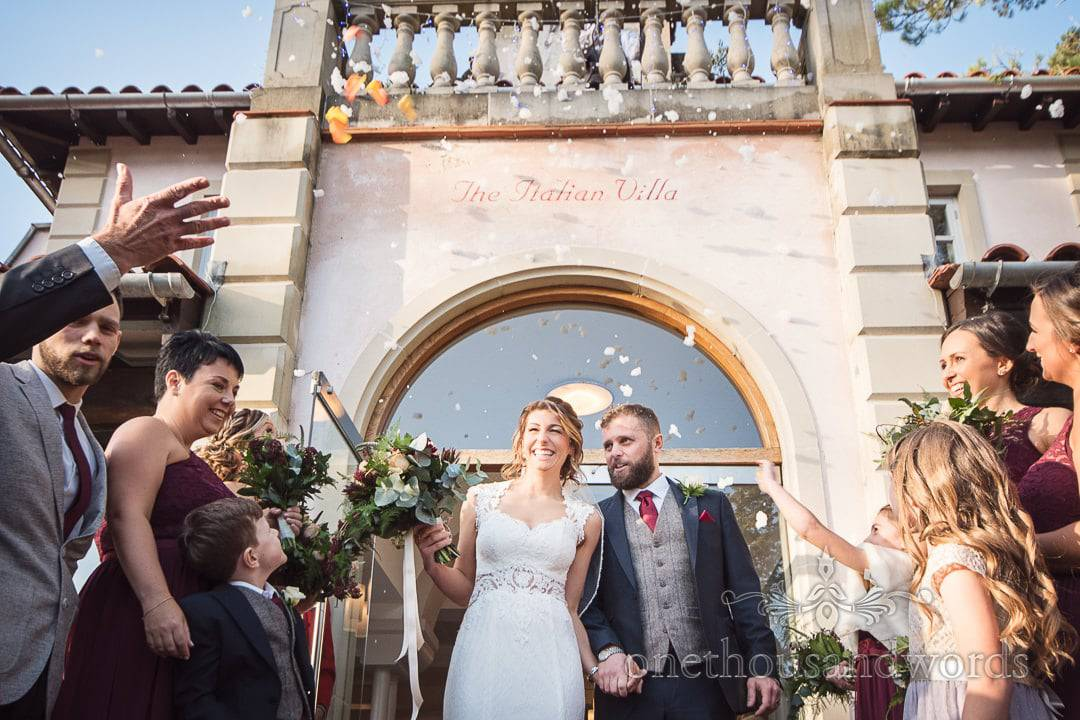 Newlyweds are showered with confetti as they ascend stairs at Italian Villa wedding photos