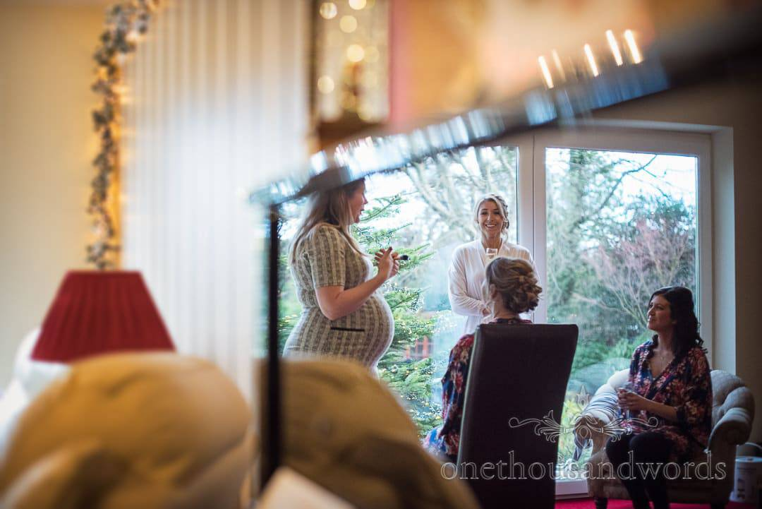Reflection of bride and bridesmaids in piano during wedding morning preparations