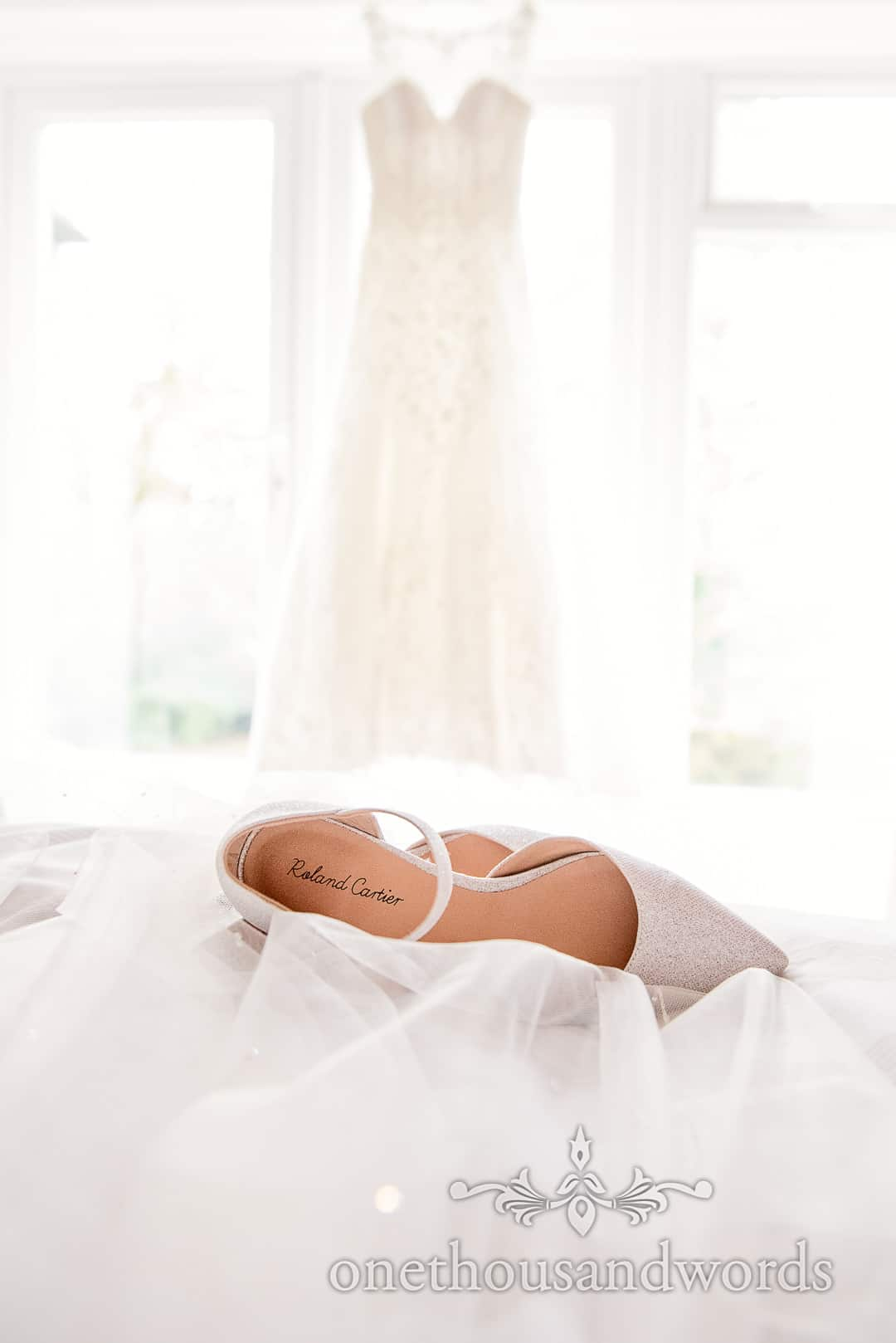 Roland Cartier white wedding shoes rest on veil with wedding dress in background