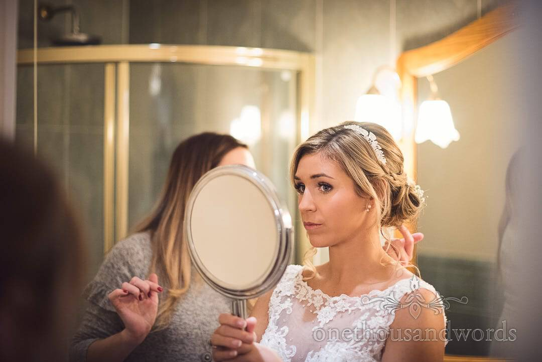 stunning blonde bride looks in make up mirror at wedding hair on wedding morning