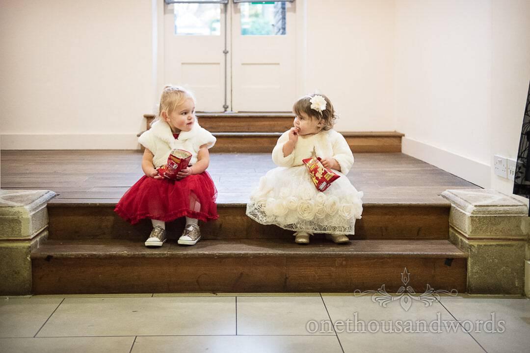 Toddler wedding guests eating crisps together on steps at The Italian Villa