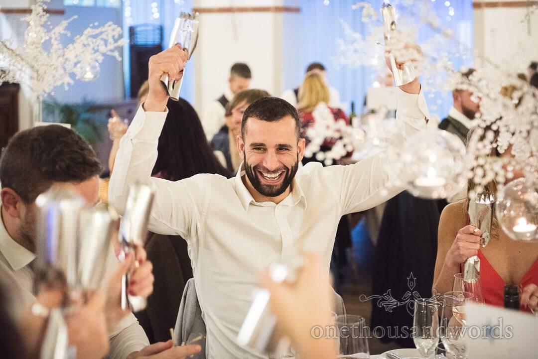Wedding guest celebrates pulling Christmas crackers at Italian Villa wedding breakfast