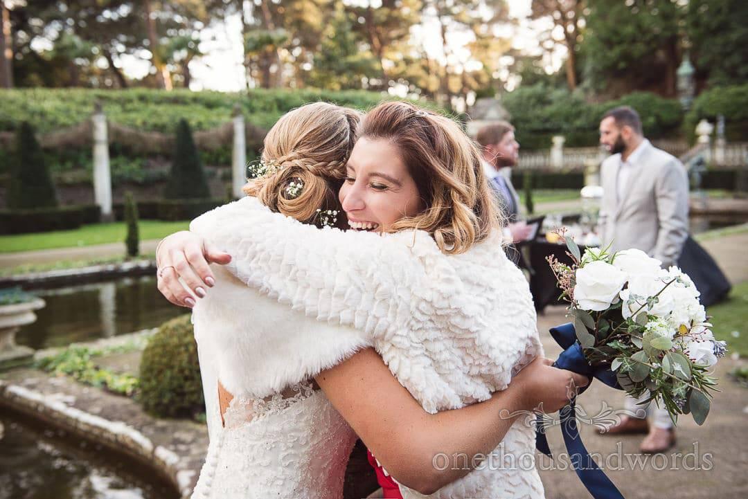 Wedding guest congratulates bride with hugs in Italian Villa gardens