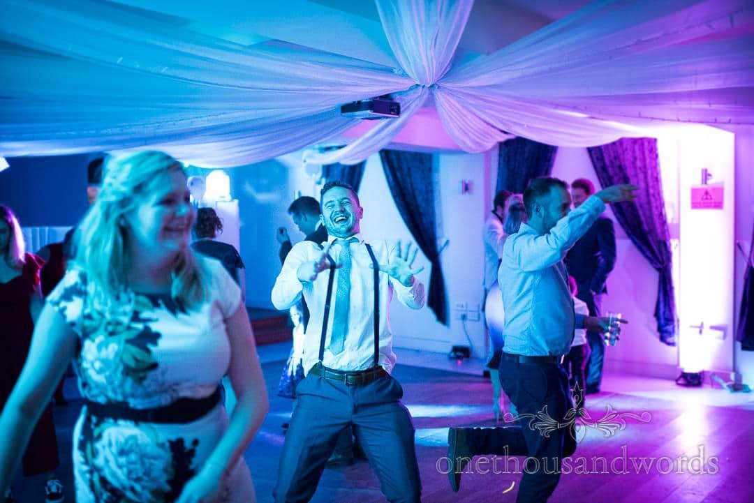 Wedding guest in braces dances under blue lights at Italian Villa Wedding venue