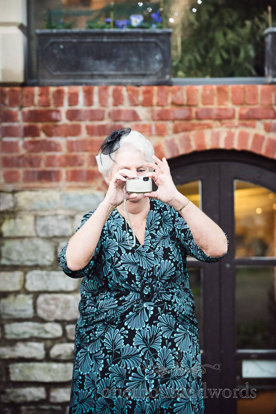 Wedding guest in floral print dress takes photos at The Italian Villa Wedding Venue