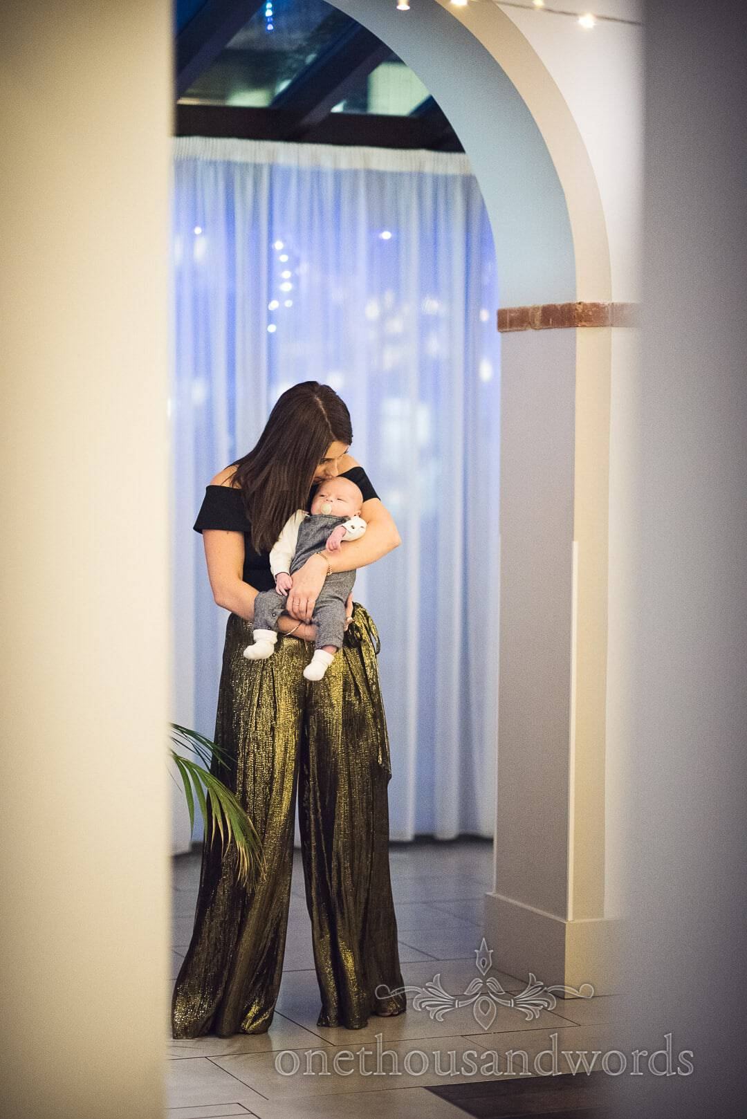 Wedding guest in gold trousers kisses baby to sleep during wedding breakfast