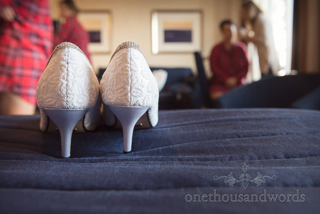 White detailed wedding shoes on the bed during bridal preparations