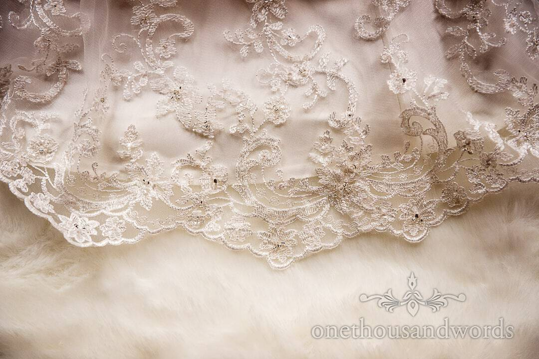 White wedding dress appliqué detail photograph with white fur shrug