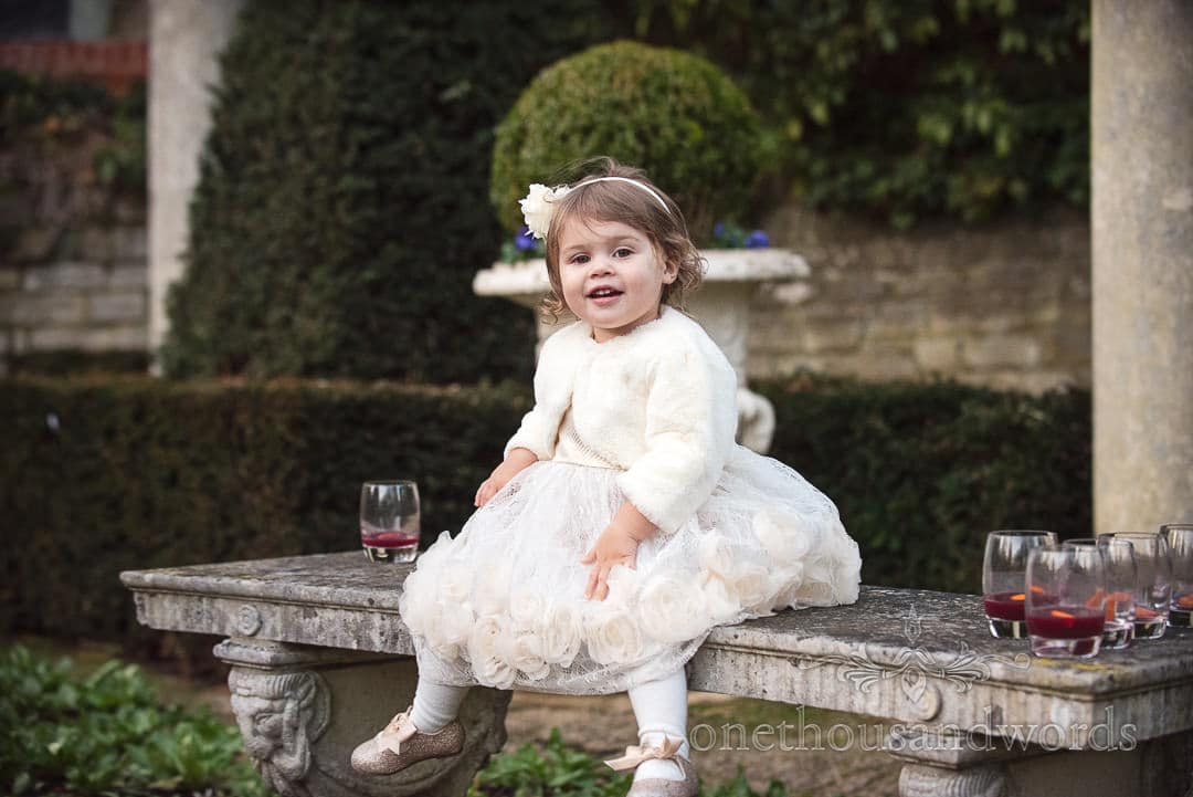 Young wedding flower girl looks after guests glasses of mulled wine at The Italian Villa