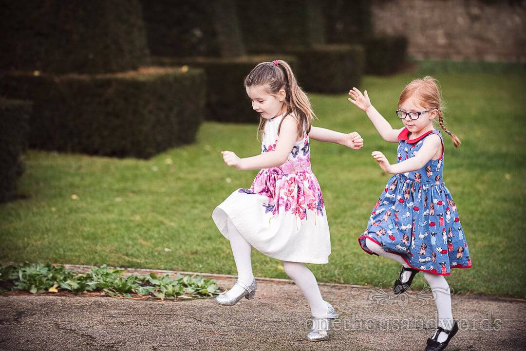 Young wedding guests skipping around the gardens at The Italian Villa Wedding Venue