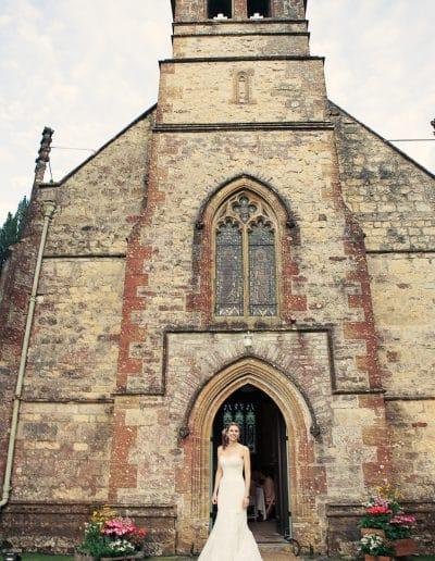 beautiful bride outside Plush Manor stone church wedding breakfast venue in Dorset