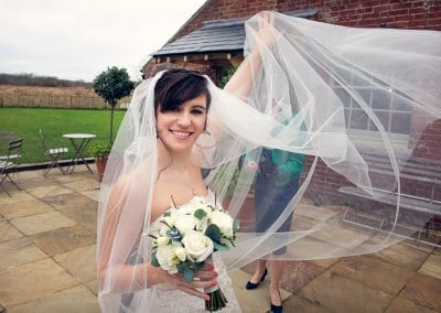 Beautiful bride with veil in the wind at Sopley Mill wedding venue