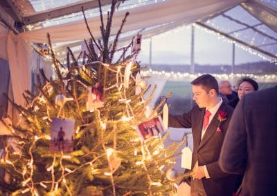 Best man at Plush Manor Winter wedding inspects the Christmas Tree in marquee