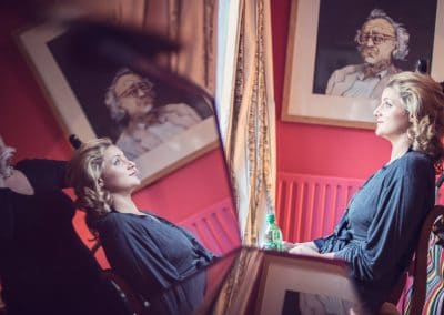 Bridal hair preparation with reflection in piano at Plush Manor wedding venue