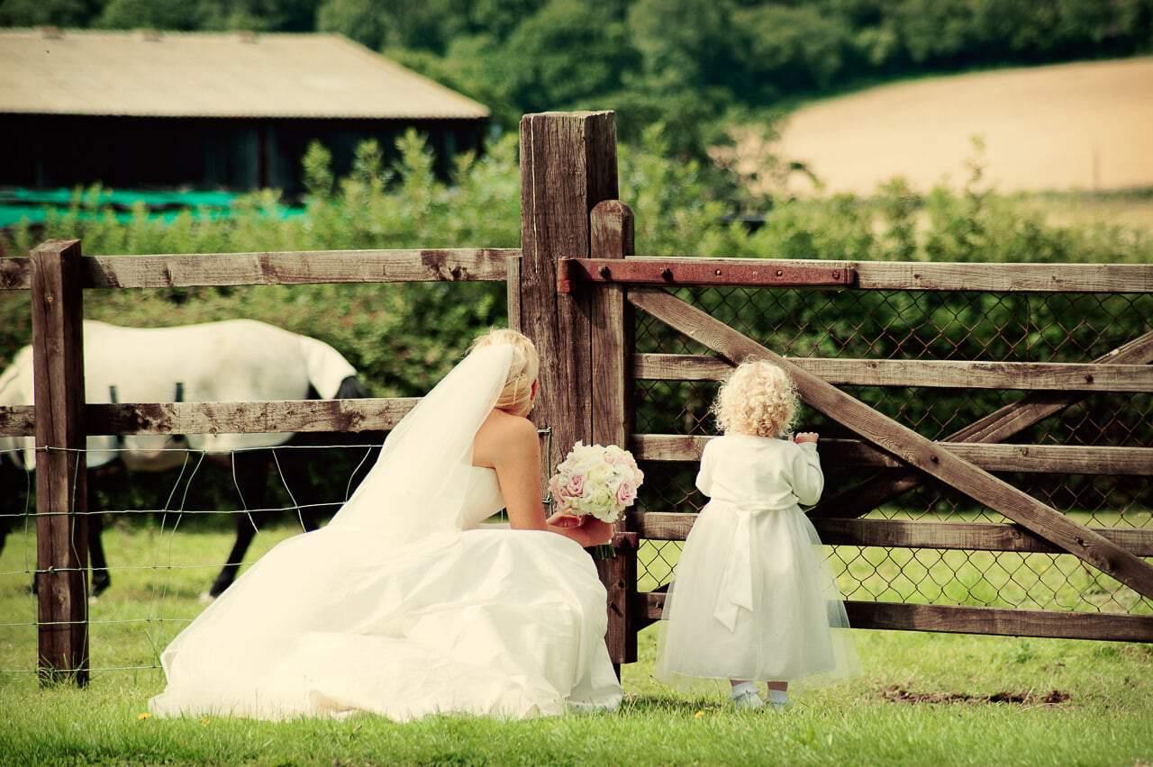 Bride and flower girl look at horses through Stockbridge Farm fence