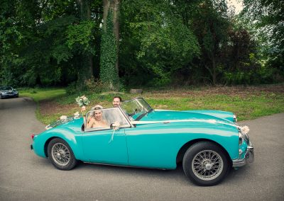 Bride and groom arrive at Plush Manor wedding in Classic blue MG wedding car