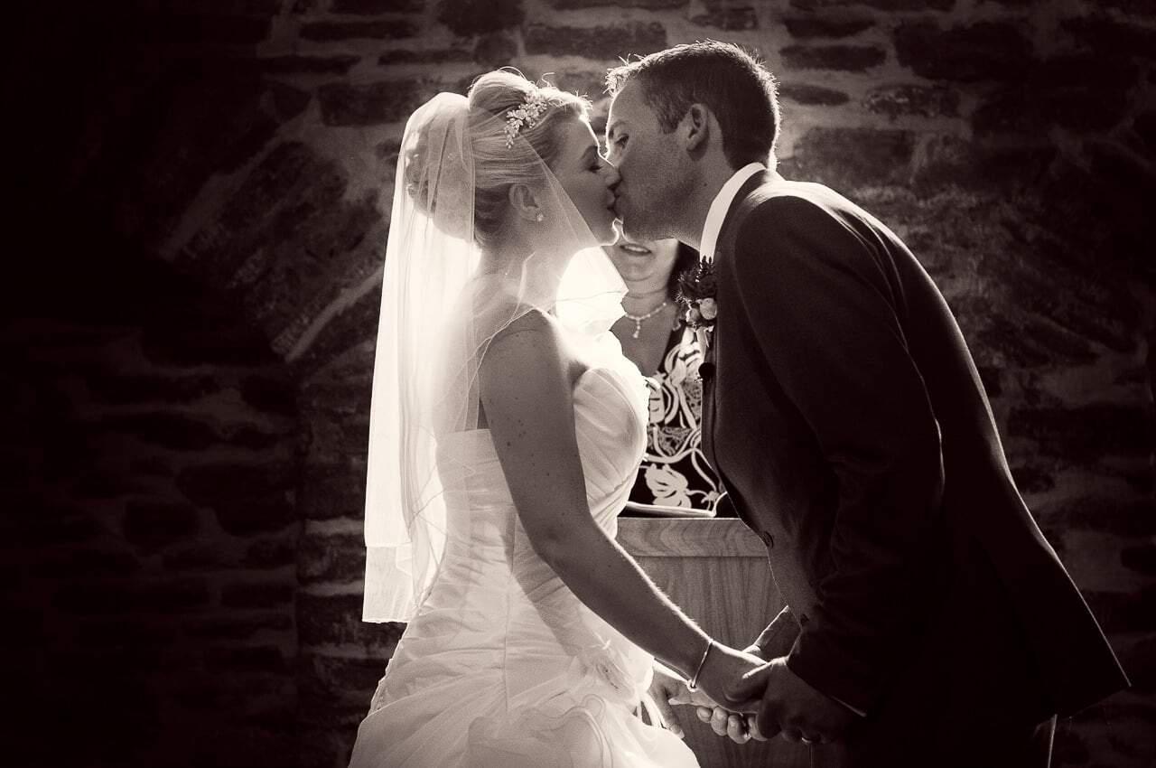 Bride and groom first kiss at Stockbridge Farm Barn Wedding photograph