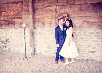 Bride and groom hug next to stone and wood of Stockbridge Farm Barn