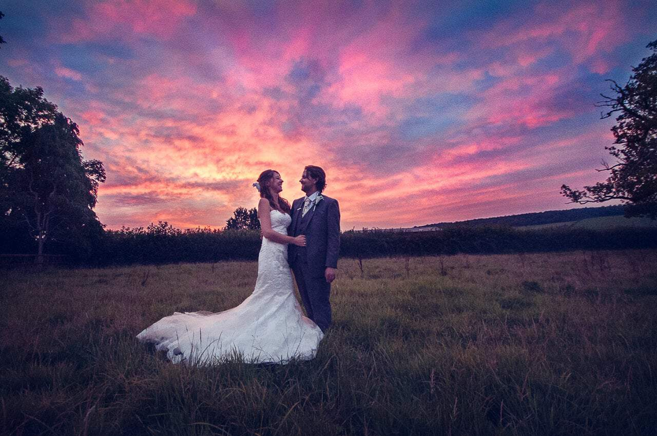 Bride and groom in Dorset countryside with epic sunset at Stockbridge