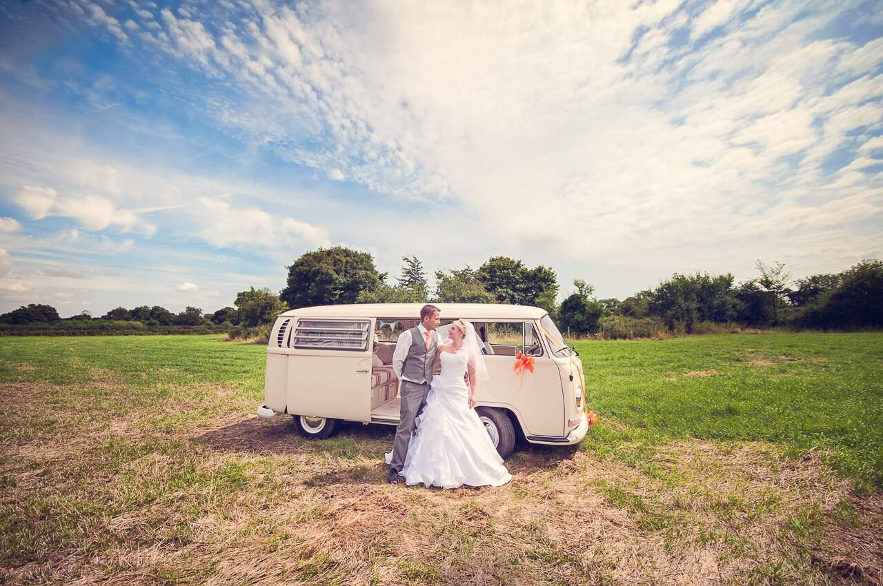 Bride and groom in Dorset countryside with white VW wedding bus