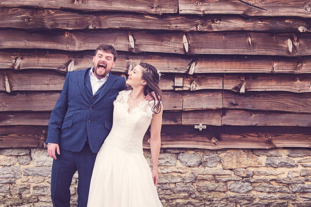 Bride and groom laughing against Stockbridge Farm Barn backdrop