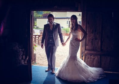 Bride and groom laughing as they enter their wedding at Stockbridge Farm Barn