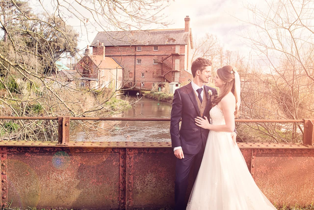 Bride and groom on rusty bridge at Sopley Mill wedding photographers