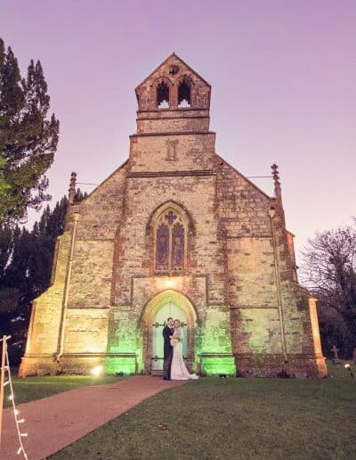 Bride and groom outside English stone church lit at night at Plush Manor Wedding