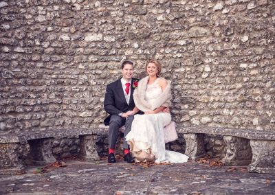 Bride and groom sit on stone bench with stone wall background at Plush Manor
