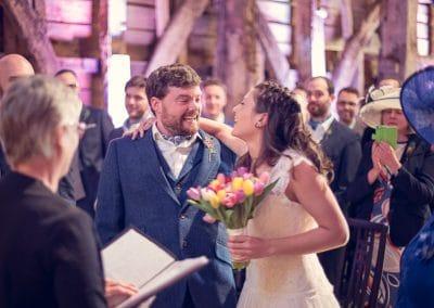 Bride and groom smiling at Stockbridge Farm Barn wedding ceremony