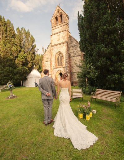 Bride and groom wait to enter wedding breakfast in stone church at Plush Manor