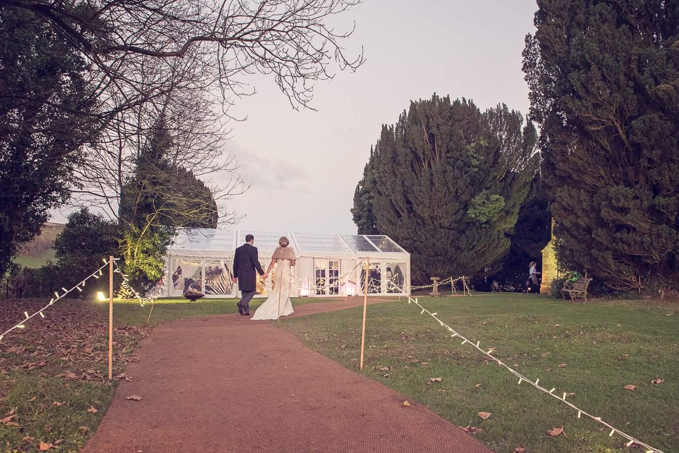 Bride and groom walking towards Plush Manor wedding wedding marquee in Dorset