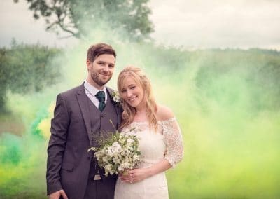 Bride and groom with green yellow smoke bombs in Dorset countryside