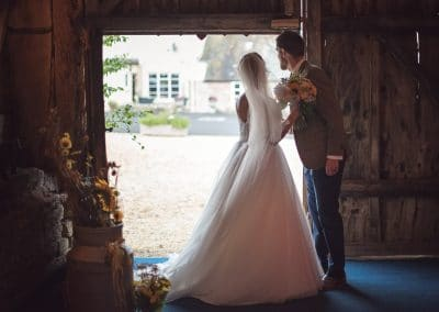 Bride and groom with sunflowers look out of Stockbridge Farm Barn