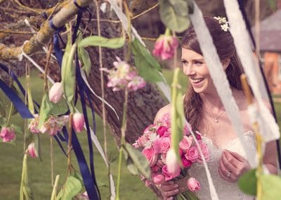 Bride at Sopley Mill wedding looks through flowers and ribbon decorations