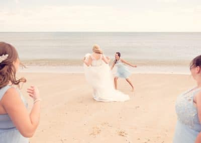 Bride and bridesmaid play together on Sandbanks Hotel wedding beach