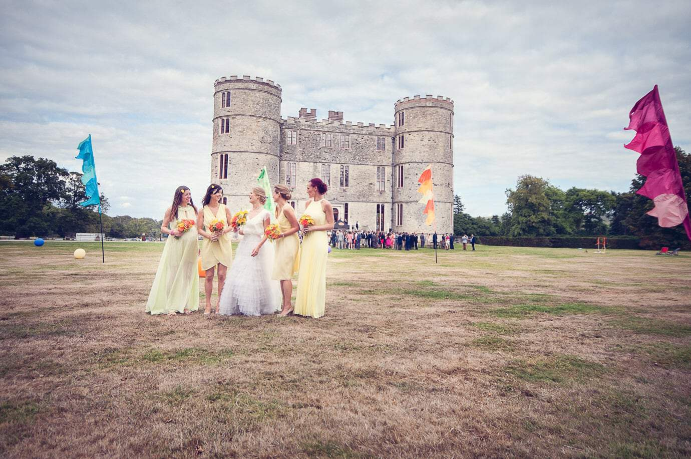 Bride and bridesmaids in the grounds with flags at Lulworth Castle summer wedding