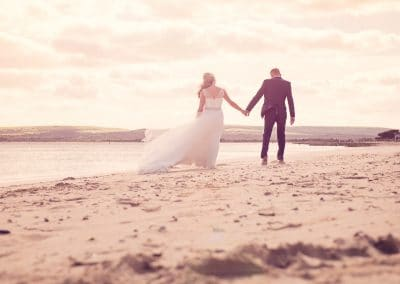 Bride and groom walk along sandbanks beach hand in hand with setting sun