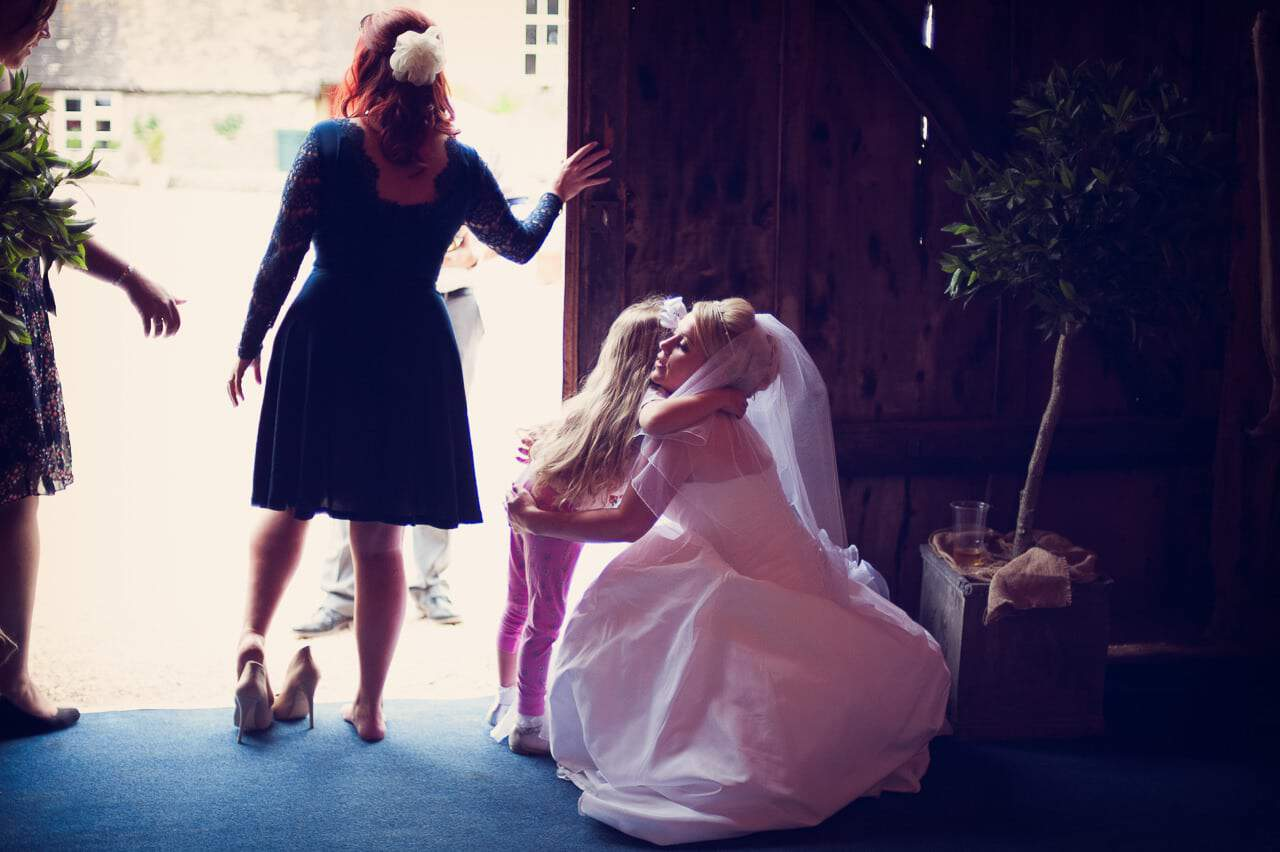 Bride hugs wedding guest in Stockbridge Farm Barn wedding venue door