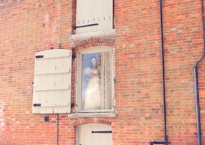 Bride in window at Sopley Mill red brick wedding venue in Dorset