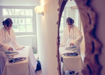 Bride irons wedding dress on wedding morning at Sopley Mill wedding venue, Dorset