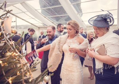 Bride looks at photographs at Plush Manor marquee wedding reception in Dorset