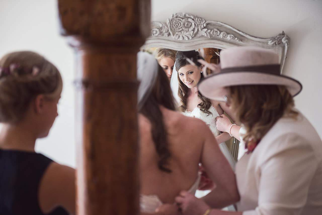 Bride looks in mirror at Sopley Mill wedding venue as she is buttoned into dress