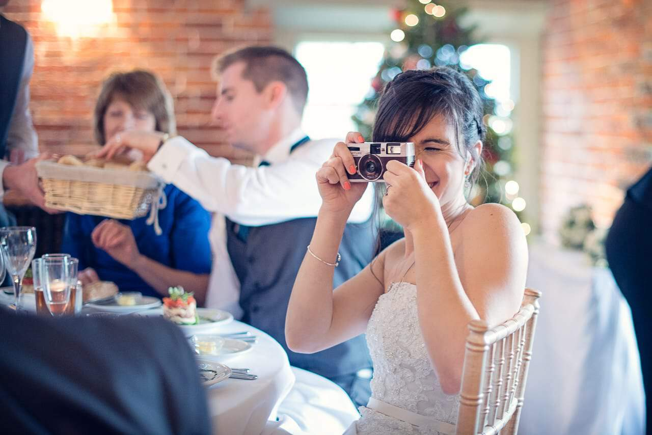Bride takes photographs with disposable camera at Sopley Mill wedding breakfast