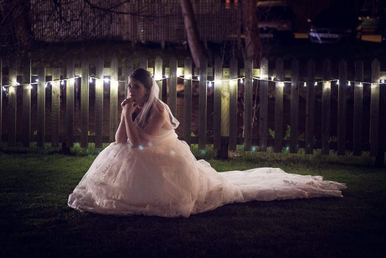 Bride waits outside Sopley Mill wedding venue at night