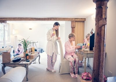 Bridesmaid opens present from bride during bridal preparations at Sopley Mill